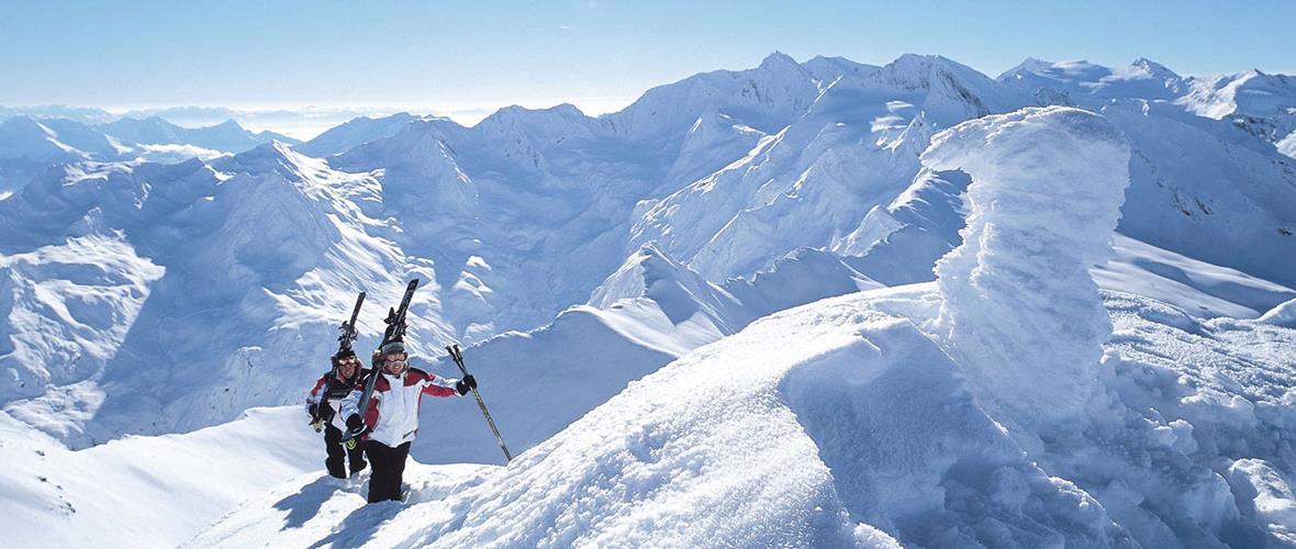 Zwei Personen bei Schneewanderung mit Ski auf der Schulter